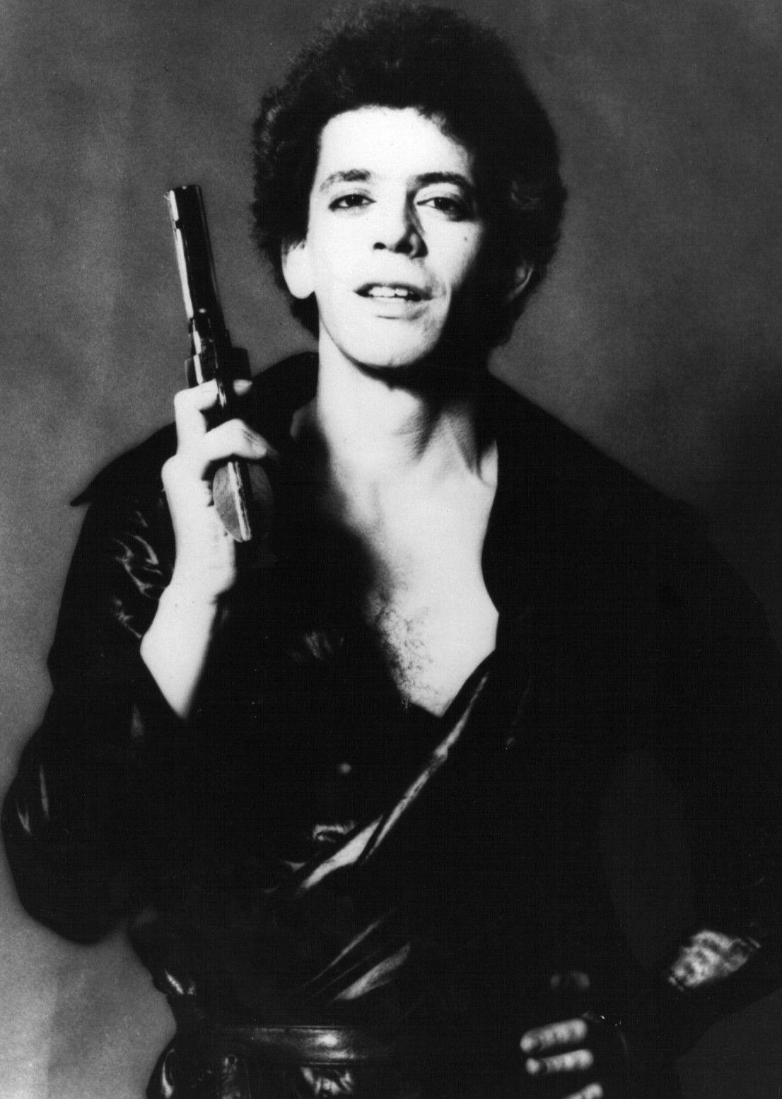 Lou Reed holding a gun during a 1977 photo shoot.